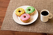 Donuts with a glaze on a white plate. Nearby is a coffee mug