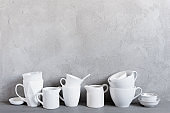 White crockery on the table against the textured grey wall
