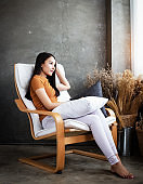 Woman sitting on chair,looking outside window,with relax feeling