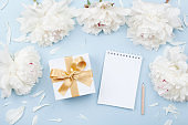 Empty notebook and gift or present box decorated white peony flowers. Flat lay composition for birthday or wedding.