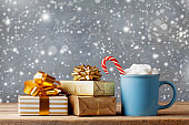 Winter lifestyle with cup of hot cocoa with marshmallows and Christmas gifts or presents on wooden background. Snow effect.
