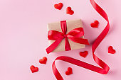 Gift box, hearts and red ribbon on pink pastel background for Valentines day card.