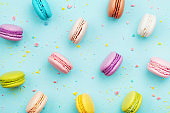 Colorful cake macaron or macaroon on turquoise pastel background from above. French almond cookies on dessert top view.