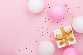 Gift or present box, balloons and confetti on pink table top view. Flat lay for birthday, mother day or wedding.