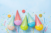 Birthday or party background. Funny balloons, candy and confetti on blue table top view. Flat lay.