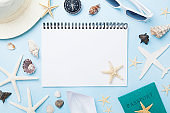 Planning summer holidays, tourism and vacation background. Travelers notebook with accessories on blue desk top view.