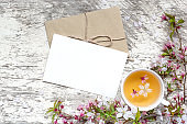 blank greeting card with cup of tea and pink spring cherry blossoming on white rustic wooden table