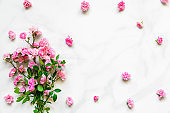 pink rose flowers bouquet with frame made of flower buds with copy space on white marble table. flat lay. top view