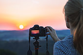 Photographer with digital camera on a tripod is taking picture of landscape.