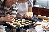 Women Spreading Butter On Cookies