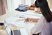 Fashion designer sketching near laptop