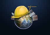 3d rendering of Earth globe apartment buildings, constriction cranes and one yellow hard hat on its surface.