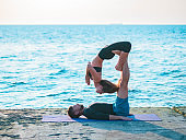 Fit young couple doing acro-yoga at sea beach. Man lying on concrete plates and balancing woman on his feet. Beautiful pair practicing yoga together