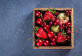 Summer Food Background. Wooden box with apples, strawberries and cherry on blue concrete table Copy space, top view