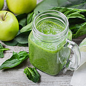 Detox concept. Spinach smoothie in mason jar. Healthy Raw Vegetarian Smoothie on wooden table. Top view, flat lay