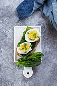 Bread sandwich with spinach and boiled eggs on ceramic plate on gray table background, top view. Healthy Food Diet Snack Concept