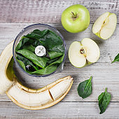 Ingredients for Green smoothie with apples, spinach and banana on wooden background table. Top view