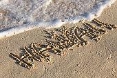 Inscription Hawaii on sandy beach with wave's foam