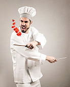 Kitchen chef with knifes cutting flying pepper