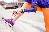 Female athlete tying shoelace