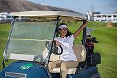 Woman in golf cart on field greeting friends
