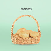 Potatoes in wicker basket on green backgroun