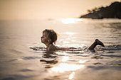 Small boy enjoying in shallow water at sea.