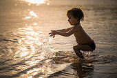 Little boy having fun while playing in shallow water at sea.