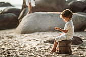 Sad little boy holding pebbles while relaxing on a beach.