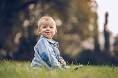 Portrait of cute small boy relaxing on the grass.