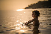 Profile view of cute boy relaxing in the sea at sunset.