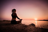 Young Zen-like woman practicing Yoga at the beach at sunset.