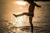 Carefree boy splashing water with his leg while standing in the sea.