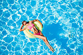 Woman relaxing on rubber ring in the swimming pool