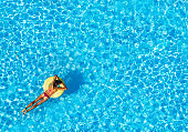 Slim woman floating on air ring in the pool