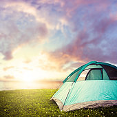 Camping tent by the lake at sunset