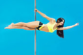 Young sexy brunette making superman element hanging on pole at blue background. Fit smiling poledancer in yellow pole outfit performing horizontal plank. Poledancing exciting fitness. Copy space.
