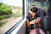 Little girl with headphones and smart phone travelling by train