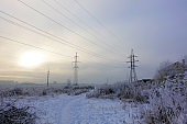 Winter. Frosty landscape. Transmission tower or electricity pylon to support an overhead power line. Russia.