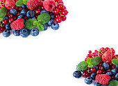 Top view. Red and blue berries. Ripe blueberries, red currants and raspberries on whitebackground. Berries at border of image with copy space for text. Various fresh summer berries on white background.