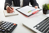 Close up view of bookkeeper or financial inspector hands making report, calculating or checking balance. Marketing strategy brainstorming