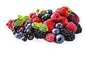 Mix berries isolated on a white. Ripe blueberries, blackberries, raspberries, currants and strawberries with mint. Berries and fruits with copy space for text. Various fresh summer berries on white background. Background berries.
