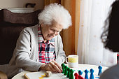 Senior woman playing Ludo game with caregiver