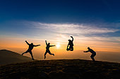 silhouette of friends jumping in sunset for happiness,fun and team work concept.