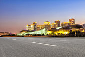 empty asphalt road and modern buildings in Zhengzhou east new district in cloud sky at night