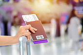 The hand of a woman holding a passport, a travel ticket, is placed on a suitcase.