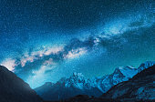 Milky Way and snowy mountains. Fantastic view with mountain ridge and starry sky at night in Nepal. Beautiful Himalayas. Night landscape with blue sky with stars and milky way. Galaxy.Space background