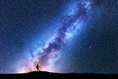 Silhouette of man with trekking poles against amazing Milky Way at night. Space background. Landscape with man on the hill, bright milky way, sky with stars. Beautiful galaxy. Travel. Starry sky