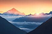 Majestic scene of silhouettes of mountains and low clouds at colorful sunrise in Nepal. Landscape with snowy peaks of mountains, beautiful sky and yellow sunlight. Rocks and sun rays.Nature background