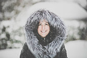 Young attractive woman wearing fur coat during snowstorm